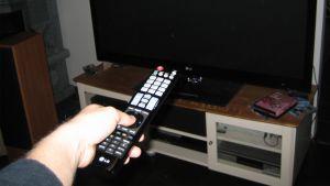 Kaukosäätimellä osoitetaan kohti televisiota.