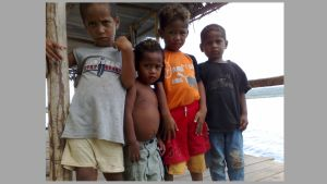 Neljä pikkupoikaa seisoo katoksessa rannalla.