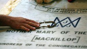 Nainen on asettanut rukousnauhan Mary MacKillopin haudan päälle.