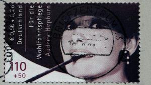 Audrey Hepburnin lähikuva postimerkissä. Kuva on elokuvasta Aamiainen Tiffanylla.