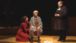 Oikealla seisova pappi ja näyttämölle polvistunut punapukuinen nainen yrittävät puhutella kivettyneenä istuvaa Niskavuoren Loviisaa.