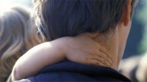 Lapsi pitää isäänsä kaulasta kiinni.