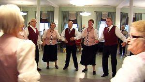 Eläkeläisryhmä esittää kansantanssin Oulun Aleksinkulmassa.