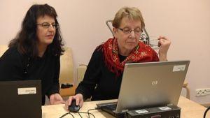 Taru Björkman neuvoo Ilona Valtosta editointiohjelman käytössä.