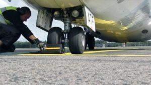 Lentoemekaanikko tarkastaa lentokonetta lentokentällä.