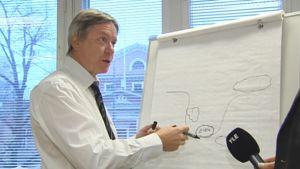 Reijo Aarnio piirtää geoscoring mallia fläppitauluun