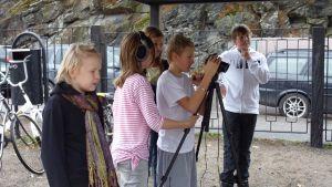 Koululaisia kuvaamassa videokameralla koulun pihassa.