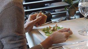 Nainen syömässä ravintolassa.