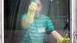 Siivooja pesee lasiovea.