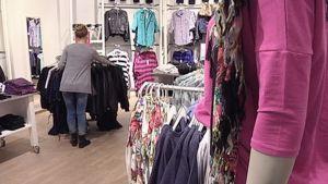Nuori nainen katselee vaatteita kaupassa.