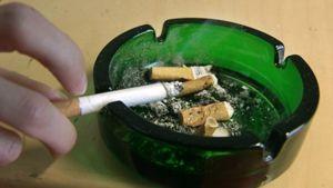 Tupakoitsija karistaa palavaa savuketta tuhkakuppiin.