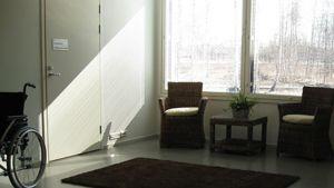 Kuvan nurkassa näkyy pyörätuoli. Aurinko paistaa ikkunasta sisään ja heijastaa varjon seinälle.