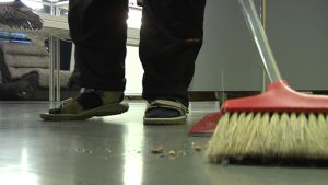 siivooja lakaisee roskia rikkalapiolla