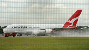 Palomiehet sammuttavat Qantasin A380-koneen rikkoutunutta moottoria.
