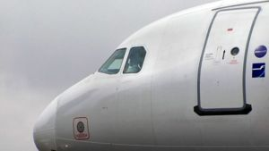 Finnairin lentäjä istuu lentokoneen ohjaamossa.