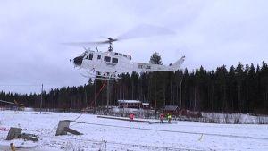 Helikopteri asentaa sähkölinjaa Lievestuoreella.