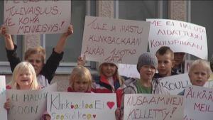 Klinkbackan koulun oppilaita osoittaa mieltään.