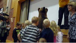 Lapset silittävät karhun turkkia.