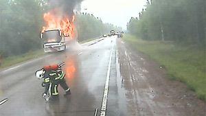 Palava linja-auto ja palomiehiä tiellä.