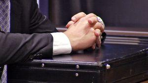 Pukuun pukeutunella mies pitää käsiään ristissä mustan salkun päällä, joka on nostettu pöydälle.