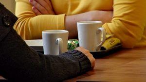 Kaksi naista kahvitunnilla valkoisten kahvikuppien ääressä.