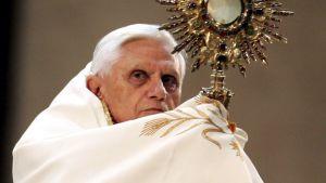 Paavi Benedictus XVI kietoutuneena kaapuunsa.