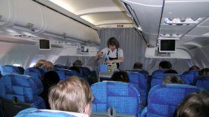 Lentoemäntä tarjoilee matkustajille lentokoneessa matkan aikana.