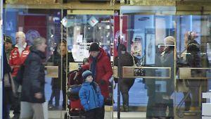 Lapsi on tulossa äitinsä kanssa tavarataloon. Ihmisiä kiiruhtamassa tavaratalosta ulos ja sisään.