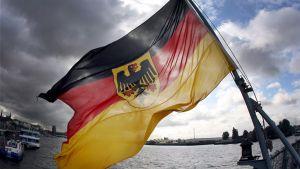 Saksan lippu heiluu puoliksi tummaa taivasta vasten.