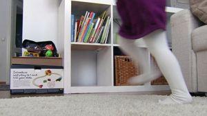 Lapsi leikkii kotinsa olohuoneessa.