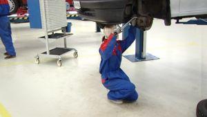 Autoasentajaksi opiskeleva nuori harjoittelee auton renkaan vaihtamista.