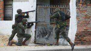 Sotilaat tähtäävät jengliäsiä aseillaan.