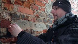 Jyrki Portin asettaa purkkikameraa tiiliseinän vieressä Vanhan Vaasan raunioilla.