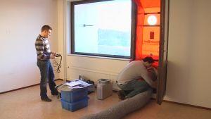Kaksi miestä tekee asunnon ilmatiiveyskoetta.