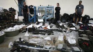 Poliiseja ja takavarikoituja aseita.