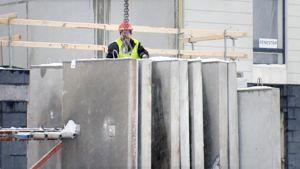 Rakennusmies työskentelee rakennustyömaalla.