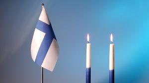 Suomen lippu ja kaksi kynttilää.