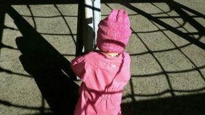 Lapsi nojaa kiipeilytelineeseen.