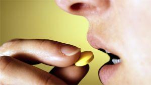 Mies laittaa pillerin suuhunsa.