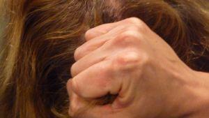 Kuvassa nyrkki ja naisen hiukset