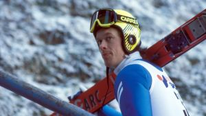 Mäkihyppääjä Jari Puikkonen kantaa suksia olallaan.