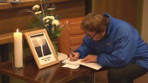 Suonenjokinen nainen kirjoittaa viestiä Kari Tapion muistokirjaan