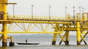 Mies kanootissa kalastelee keltaisten öljyputkien alapuolella.