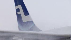 Finnairin lentokoneen pyrstö lumisateessa Helsinki-Vantaan lentokentällä.