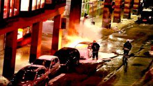 Palomiehet sammuttavat vaahtosammuttimella toista räjähtäneistä autoista Tukholman Drottninggatanilla.