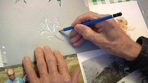 Koristekuvio syntyy sabloonan avulla ikääntyneiden taidepajassa.