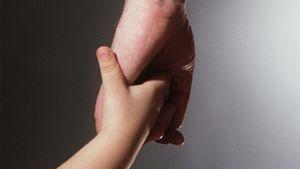 Lapsi pitää aikuisen kädestä.