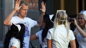 Veijarit-elokuvassa näyttelevä Antti Luusuaniemi on nostanut kätensä ylös, kun häntä on tullut piirittämään ryhmä nuoria hoitajia sairaanhoitoasuissaan.