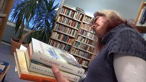 Kirjastovirkailija valikoi kirjoja hyllystä