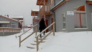 Nainen nousee lomamökin portaita lomamökin terassille